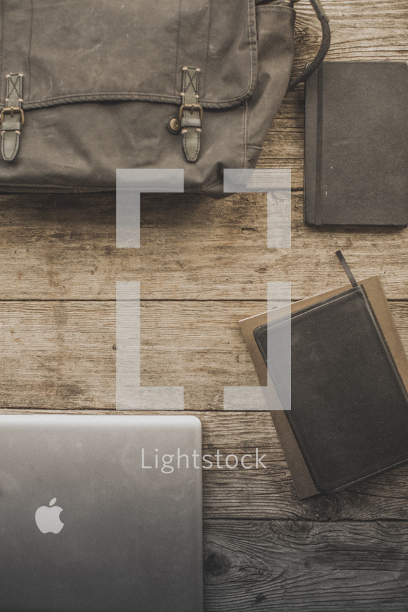 Laptop, bag, Bible and notebooks on a table