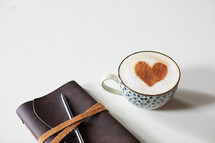 cinnamon heart in a coffee cup, Leather bound Bible, and pen