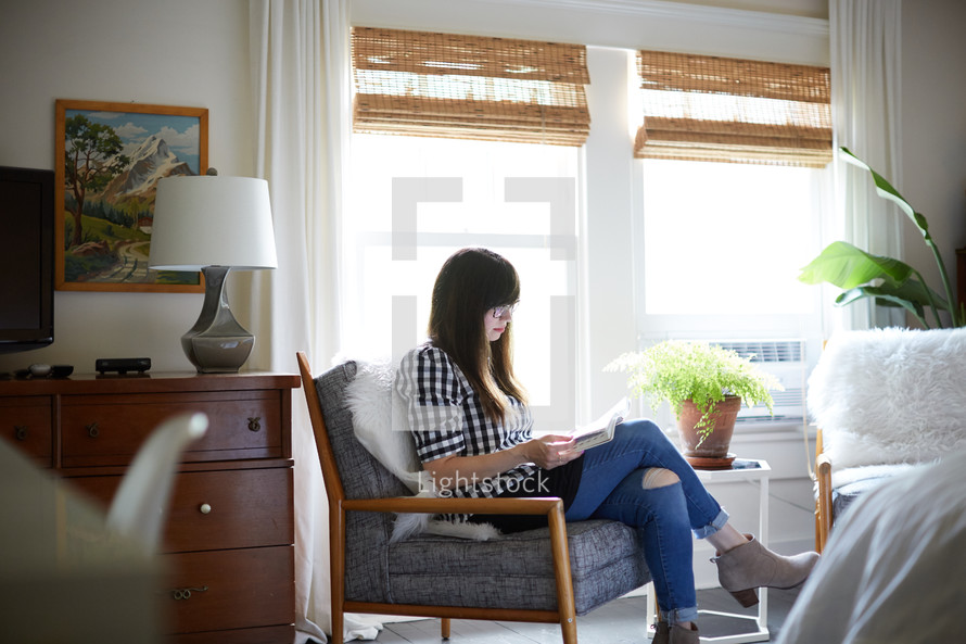 a woman sitting in a chair reading a Bible
