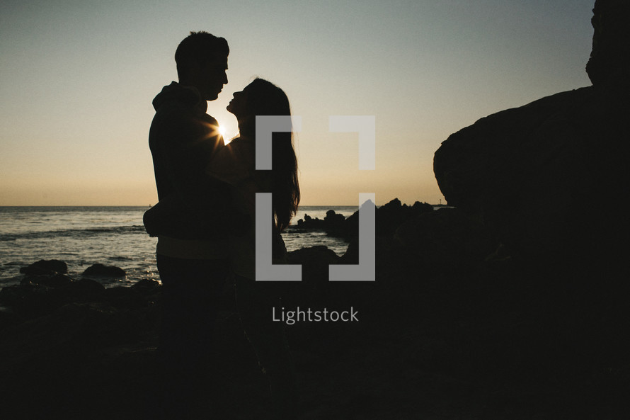 silhouette of a couple hugging on a beach