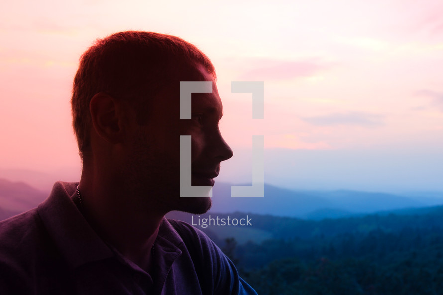 side profile of a man with mountains in the background