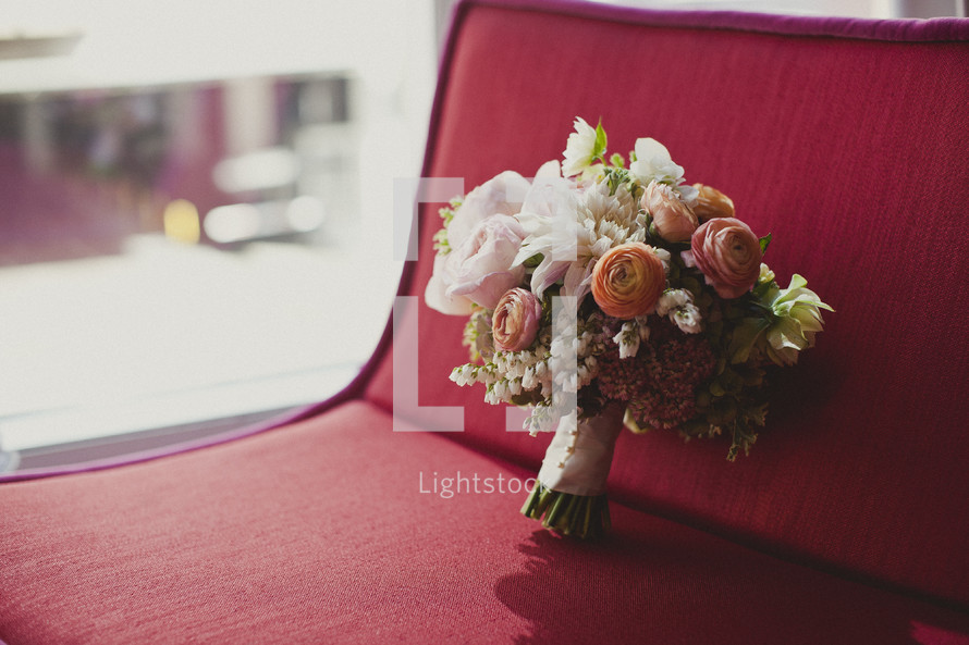 A bouquet of flowers resting on a red couch