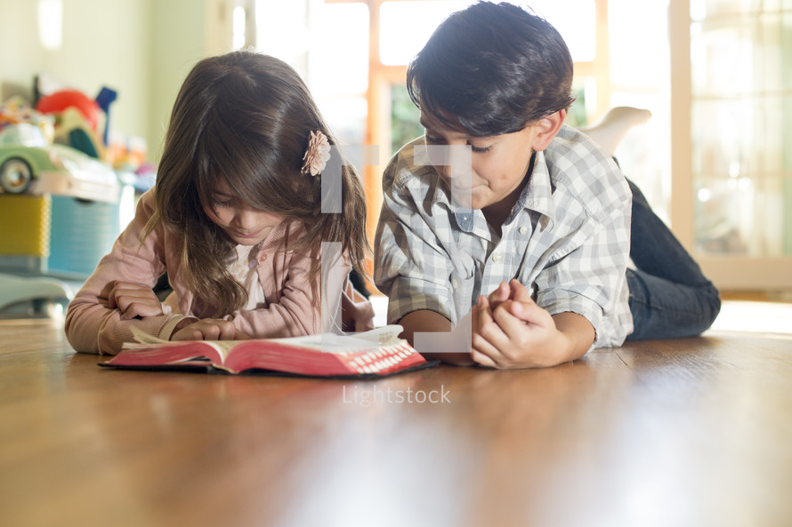 Children lying on the floor reading a Bible.