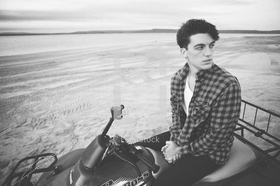 man sitting on a four wheeler on the beach