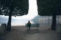 a woman sitting on a park bench looking out at a bay under fog