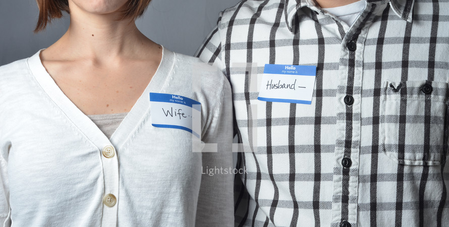 man and woman wearing name tags that read husband and wife