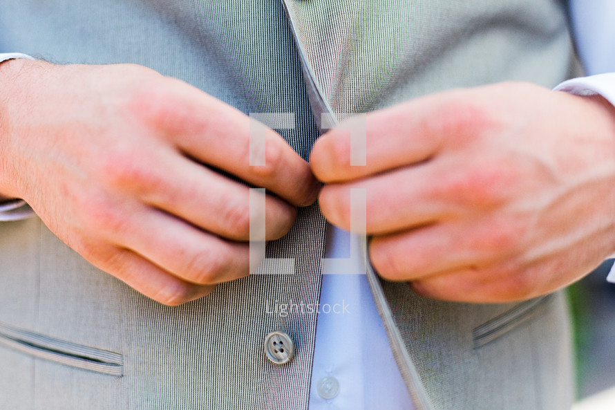 A man buttoning his suit groom wedding menswear fashion jacket