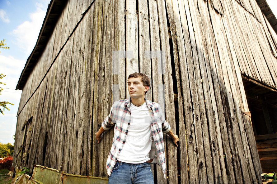 A man leaning against an old barn