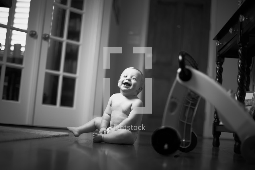A smiling little boy sits on the floor.