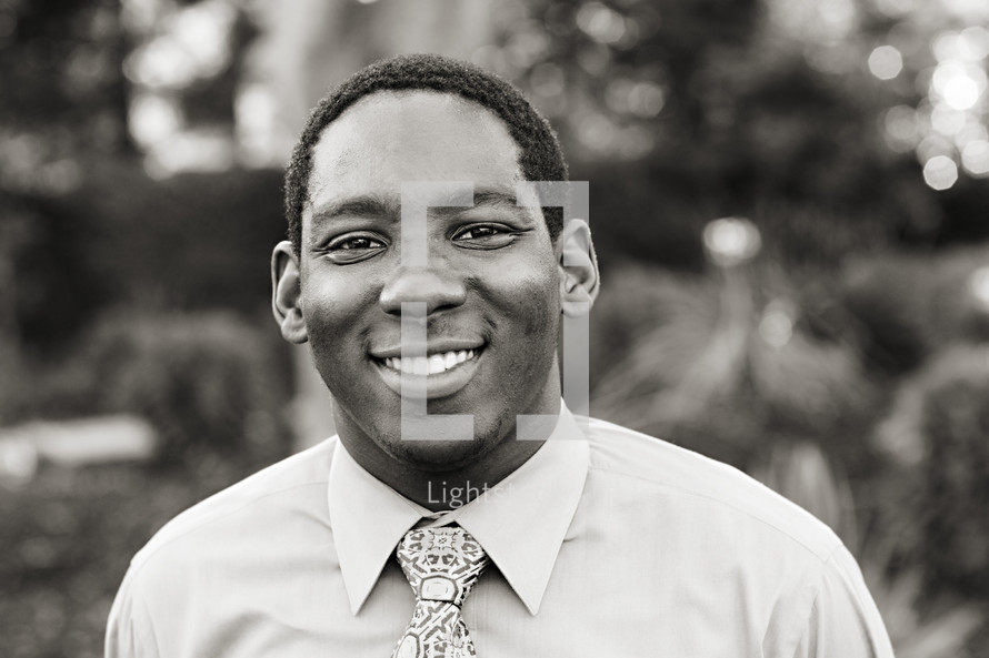 A smiling young man in a shirt and tie African American