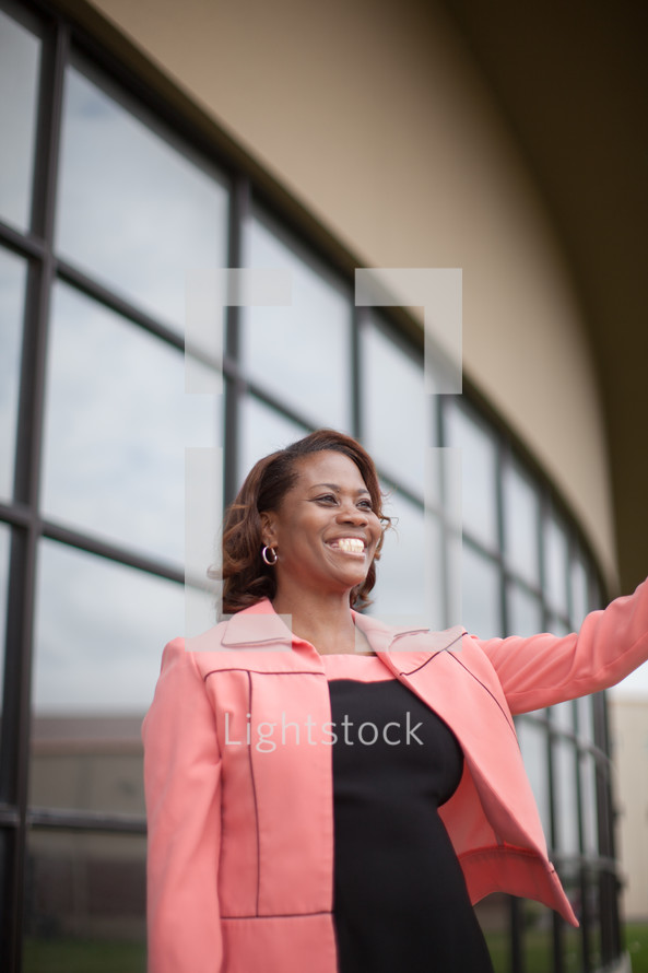 African-American woman standing at a church entrance welcoming others