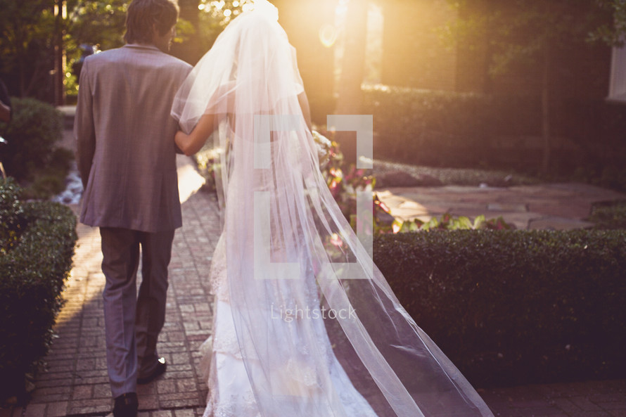 A bride and groom walking into the sun