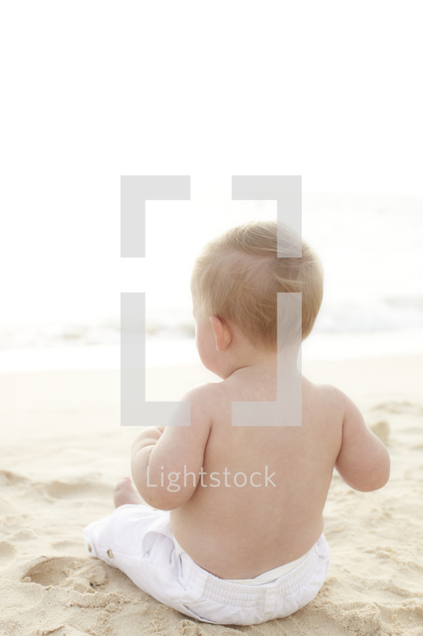 A little boy sitting on the beach looking out at the ocean.