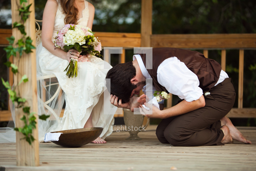 groom washing and kissing the feet of his bride photo by daniel