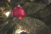 red glittery ornament on a Christmas tree