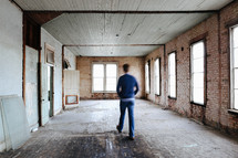 a man walking through a house that is being remodeled