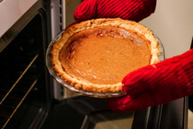 taking a pumpkin pie out of the oven
