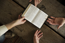 men at a Bible study with an open Bible
