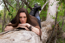 woman lying on a fallen tree