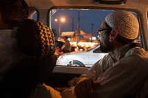 a muslim man in a prayer cap riding in the back of a car
