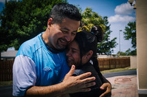A girl and her pastor embrace after being baptized.