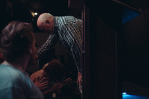 A pastor praying for and laying hands on a member of his congregation.