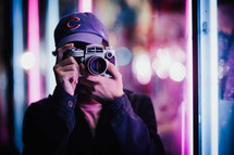 a man taking a picture with a camera at night