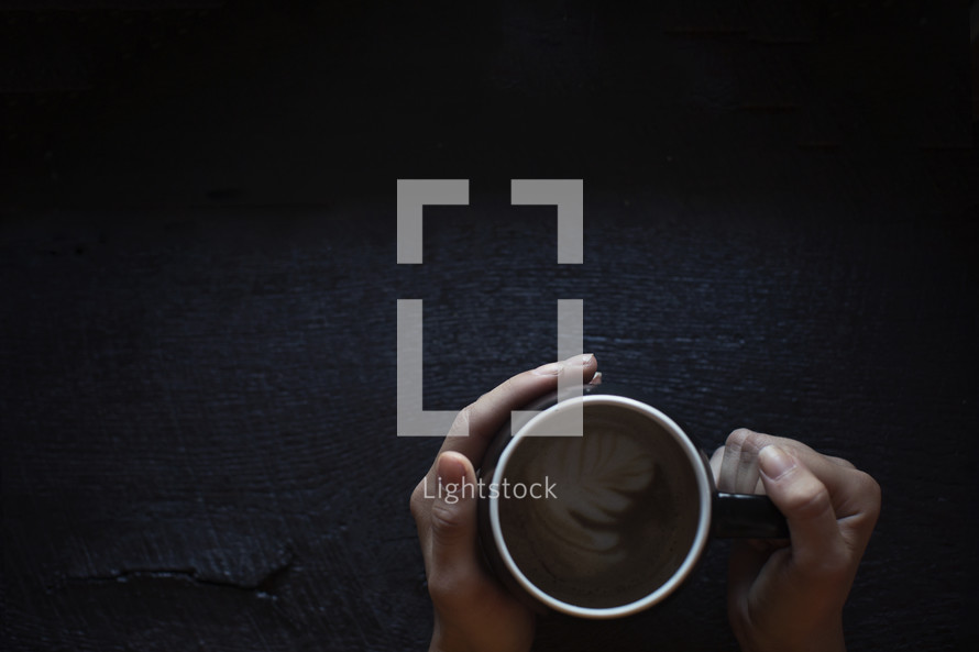hands holding a coffee mug on dark wooden table.