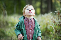 a toddler boy outdoors in a jacket looking up