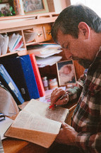 a man sitting at a desk reading a Bible