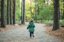 a toddler boy standing outdoors in a jacket
