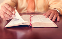 Hands turning the pages of a Bible on wooden table.