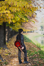 a teen boy walking with a guitar outdoors