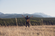 a man with a guitar standing in a field with open arms and a mountain view