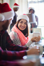 A woman in a santa hat smiling and drinking coffee