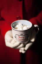 A woman's hands wearing white gloves holding a cup of hot chocolate