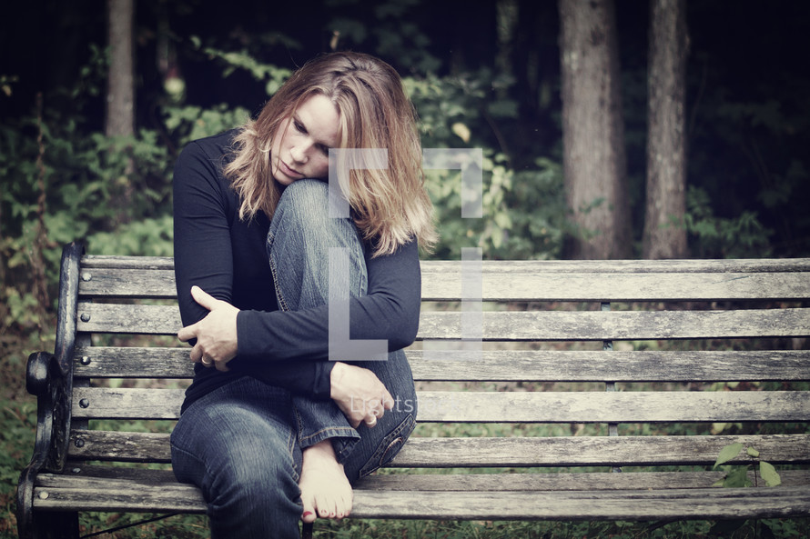sad woman sitting on a park bench