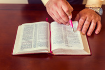 Hands with a pen on an open Bible.