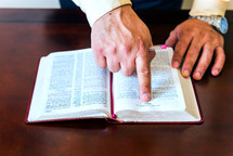 Hands on an open bible with finger pointing to scripture.