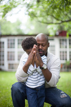 father and son with praying hands