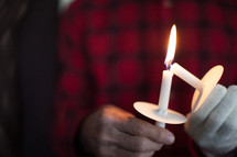 Hands lighting candles at a candlelight service