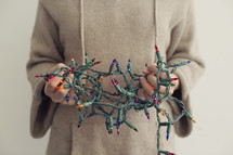 man holding tangled Christmas lights