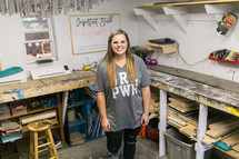 a young woman standing in a workshop