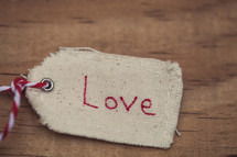 "A Christmas gift tag reading ""Love,"" on a wood grain background."