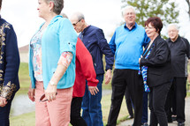 senior citizen fellowship group walking together in a park