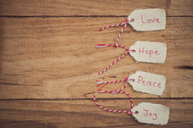 "Christmas gift tags labeled ""Love, Hope, Peace, and Joy, on a wood grain background."