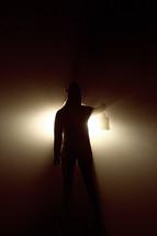 man holding a lantern lighting the way