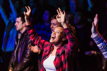 audience with raised hands singing songs of praise