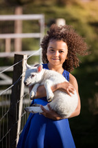 a girl holding a lamb