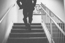 A man running up stairs in a tuxedo